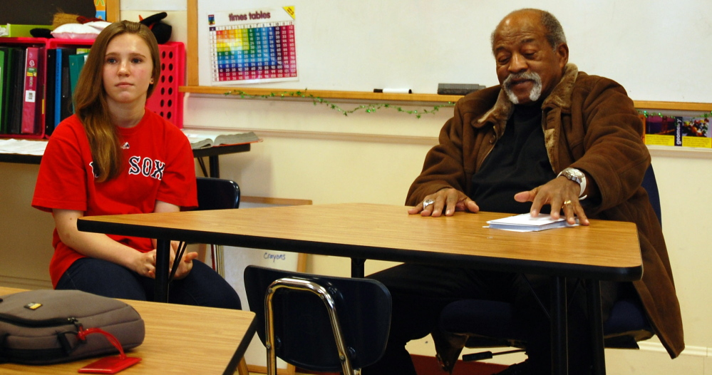 Karissa Kenyon, an eighth-grader at Wells Junior High School sits at the front of the class with former Red Sox pitcher Luis Tiant, a native Cuban who spoke with students as part of a class project on immigration. Karissa did a project detailing immigration's effect on Major League Baseball.