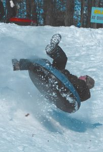 MARC MAGNO GOES AIRBORNE after hitting a jump at Foreside Field on Wednesday. The hill swarmed with children, many with adults, after Tuesday's major snowstorm. Good news for these sledders, at least, is that more snow is predicted for tonight into Friday. For the latest Mid-coast region weather forecast, see page A10.