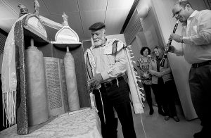 ISRAELI FOREIGN MINISTRY worker Yitshak Ozeri, center, stands next to an ancient Torah scroll prior to a dedication ceremony at the Israeli Foreign Ministry in Jerusalem on Thursday. The scroll that Israeli experts said was written 200 years ago has taken an unusual and mysterious journey from Baghdad to Jerusalem where it was greeted with candies and song in a jubilant dedication ceremony Thursday.