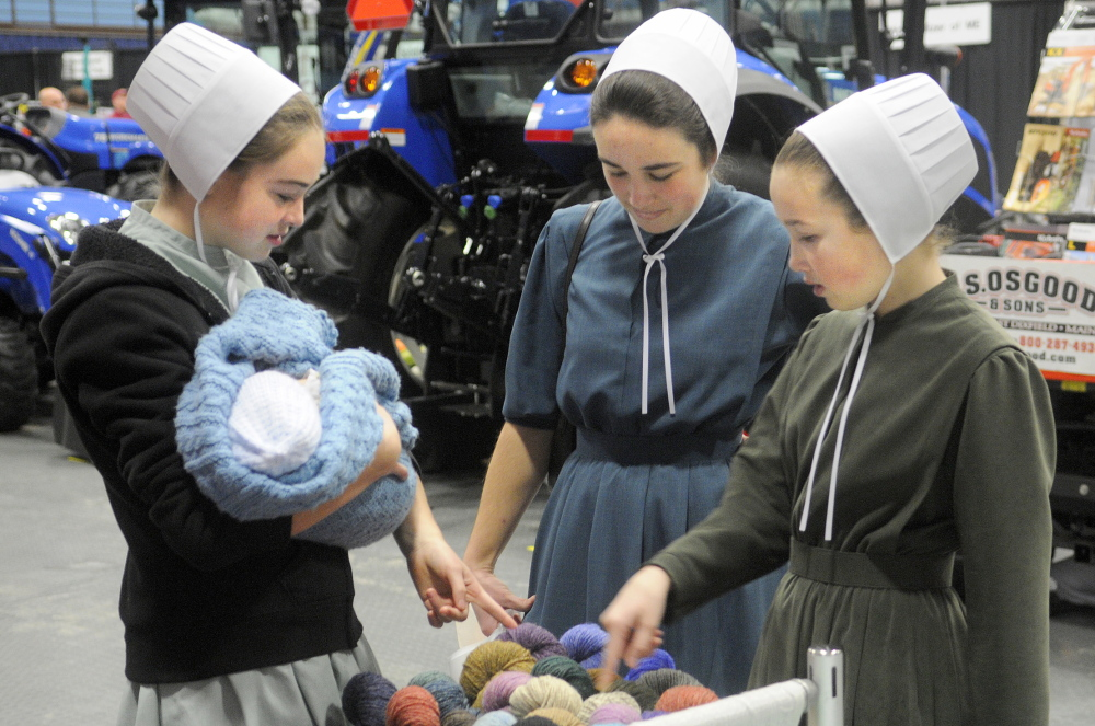 Lilia, left, Cassia and Moriah Higgins inspect yarn on display on the first day of the 2014 Agricultural Trades Show at the Augusta Civic Center. This year's show is expected to draw 5,000 attendees.