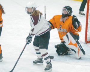 BRUNSWICK HIGH SCHOOL goalie Jordan Van Savage (right) prepares to block a shot against Greely during Wednesday's high school girl's hockey playoff opener. The Dragons fell 14-1 and were eliminated from the postseason.