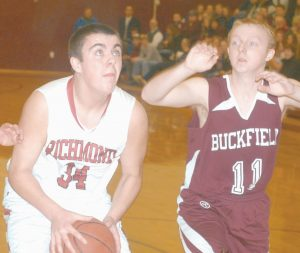 RICHMOND'S ZACH SMALL (34) looks to the hoop, with Buckfield's Jared Eastman looking to make a block during Wednesday night's preliminary playoff game against Buckfield. The Bobcats advanced to the Western D quarterfinals with the 51-40 victory.