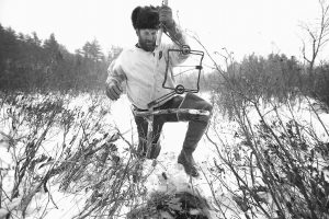 BRIAN COGILL sets a trap in a hole he chopped in the ice at a pond in Limington. Cogill is one of a shrinking number of fur trappers who have seen the prices of fur drop due to market slowdowns in big fur-buying countries like Russia, China and Korea.
