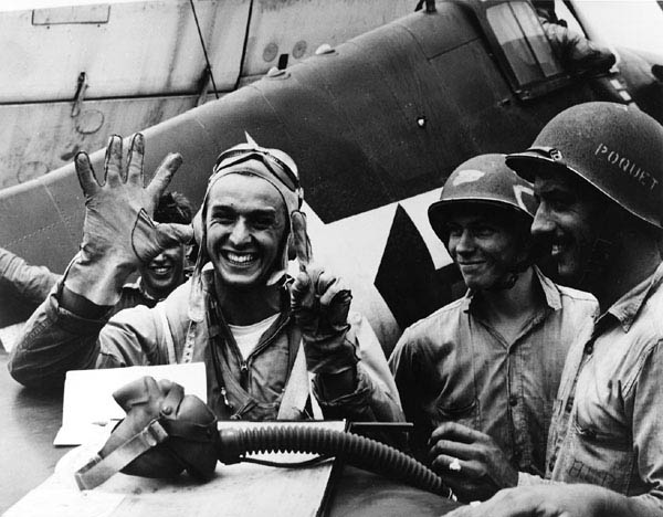 "Alex Vraciu signals six kills following his ""Turkey Shoot"" mission in Great Marianas on June 19, 1944. He downed six dive bombers in eight minutes. U.S. Navy photo"