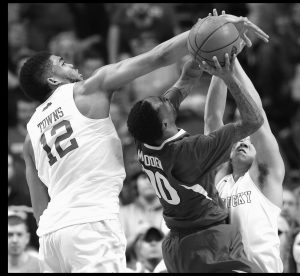 ARKANSAS GUARD Rashad Madden (00) shoots against Kentucky forward Karl-Anthony Towns (12) and Kentucky guard Devin Booker (1) during the first half of the NCAA college basketball Southeastern Conference tournament championship game on Sunday in Nashville.
