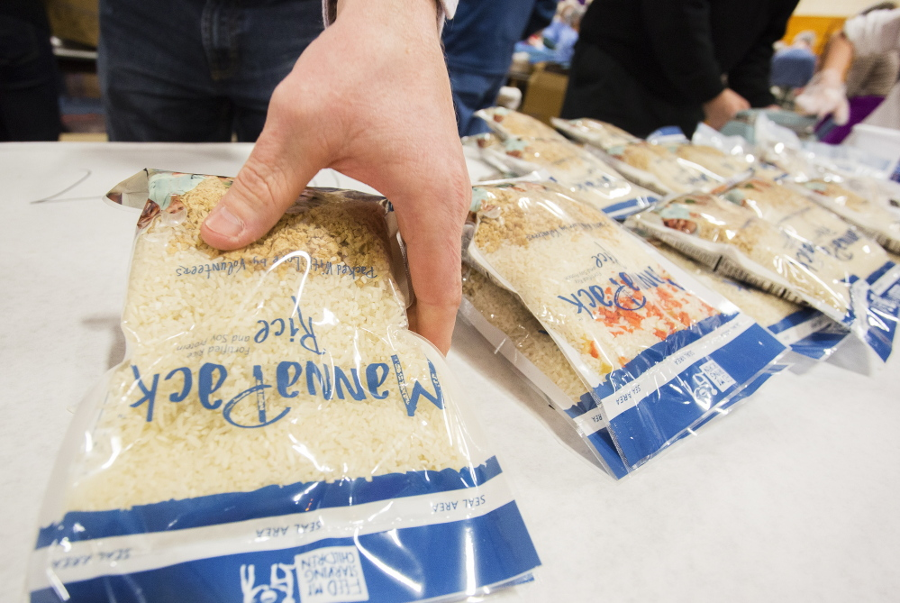 A volunteer finishes meal packs, assembled for starving children around the world, at Deering High School in Portland on Sunday.