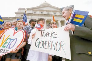 KRISTEN HOOPER, center, and Robert Loyd, right, hold a sign on the steps of the Arkansas state Capitol thanking Arkansas Gov. Asa Hutchinson for calling for changes to a religious objection measure in Little Rock, Ark., Wednesday, April 1. The measure faced a backlash from businesses and gay rights groups.