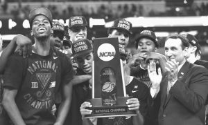 DUKE PLAYERS CELEBRATE with the trophy after their 68-63 victory over Wisconsin in the NCAA Final Four college basketball tournament championship game on Monday in Indianapolis.