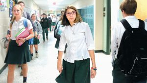 BISHOP ENGLAND HIGH SCHOOL student Christina Rivera, center, walks down the hall with her high school classmates as they change class.