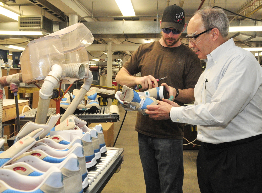 Jason Flanders, left, tells U.S. Rep. Bruce Poliquin, R-2nd District, about the model 998 shoes he's making during a tour of the New Balance factory on Friday in Norridgewock.
