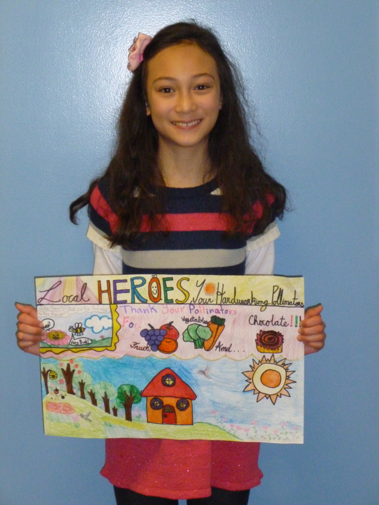 Lilly Curtis, a Hope Elementary School fifth-grader, poses with her winning poster submission for the Knox-Lincoln Soil & Water Conservation District's stewardship-themed contest. The work will advance to the state level of competition.