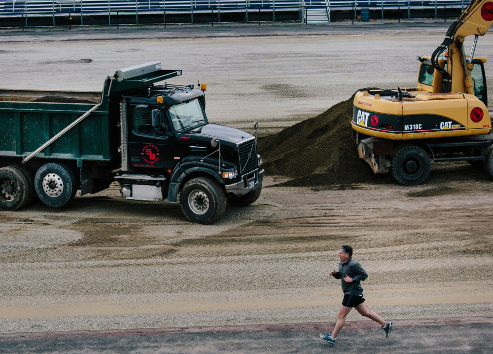 Paul Pietropaoli runs the track at Fitzpatrick Stadium while Northeast Turf of South Portland works on installing a new  artificial field. The $1 million project follows a bleacher replacement three years ago and a lighting overhaul in 2013.