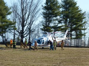 Rescue personnel finish loading 84-year-old Gilbert Tarbox into a LifeFlight helicopter bound for Central Maine Medical Center in Lewiston. DARCIE MOORE/THE TIMES RECORD