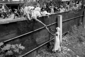 SCHOOL CHILDREN hand out food to a Rohingya young girl from outside the fence of a temporary shelter in Bayeun, Aceh province, Indonesia, today.
