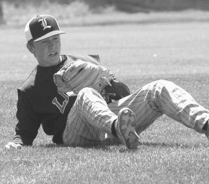 LISBON SHORTSTOP Ryley Austin rolls over after making a diving catch of a line drive in a 10-1 loss to Winthrop on Saturday in Lisbon Falls. The Greyhounds fell to 10-3 and host St. Dom's today at 4:30 p.m.