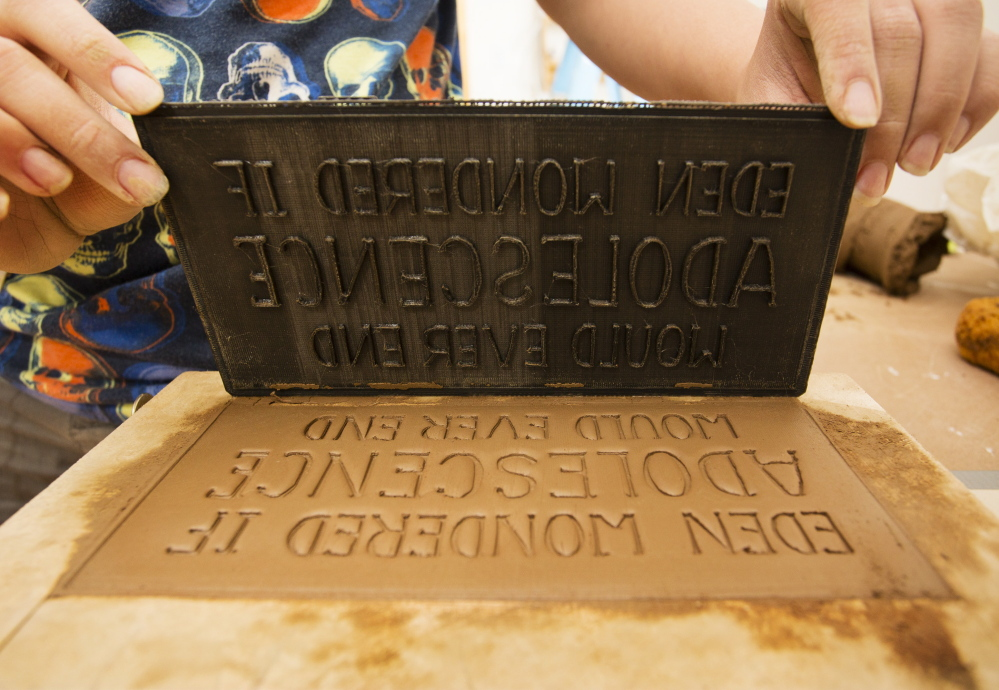 Artist Rochelle Garcia lifts a type mold after imbedding its impression into a brick created to tell stories about the India Street neighborhood and be installed, becoming a decorative part of the area.