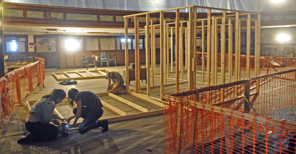 Kelly Rioux, left, Caroline Losneck and Chris Byron built a frame for a house that will be part of an art installation next month at the Colonial Theater in Augusta.