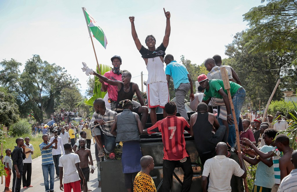 Demonstrators climb aboard a military truck as they celebrate what they perceive to be an attempted military coup d'etat, with army soldiers riding in an armored vehicle in the capital Bujumbura, Burundi Wednesday.