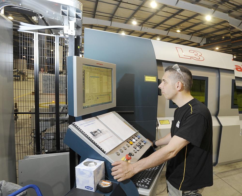 Operator Maurizio Cigarini sets up one of the high-tech laser machines that will help produce many of the parts at Modula storage products.