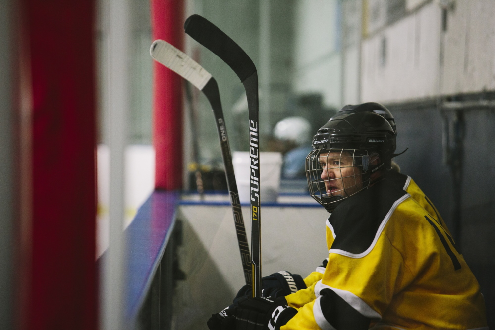 """Gibson Fay-LeBlanc watches the action from the bench during a recent game at the Portland Ice Arena. He's working on a collection of hockey-themed poems that will be called """"Deke.""""  Whitney Hayward/Staff Photographer"""
