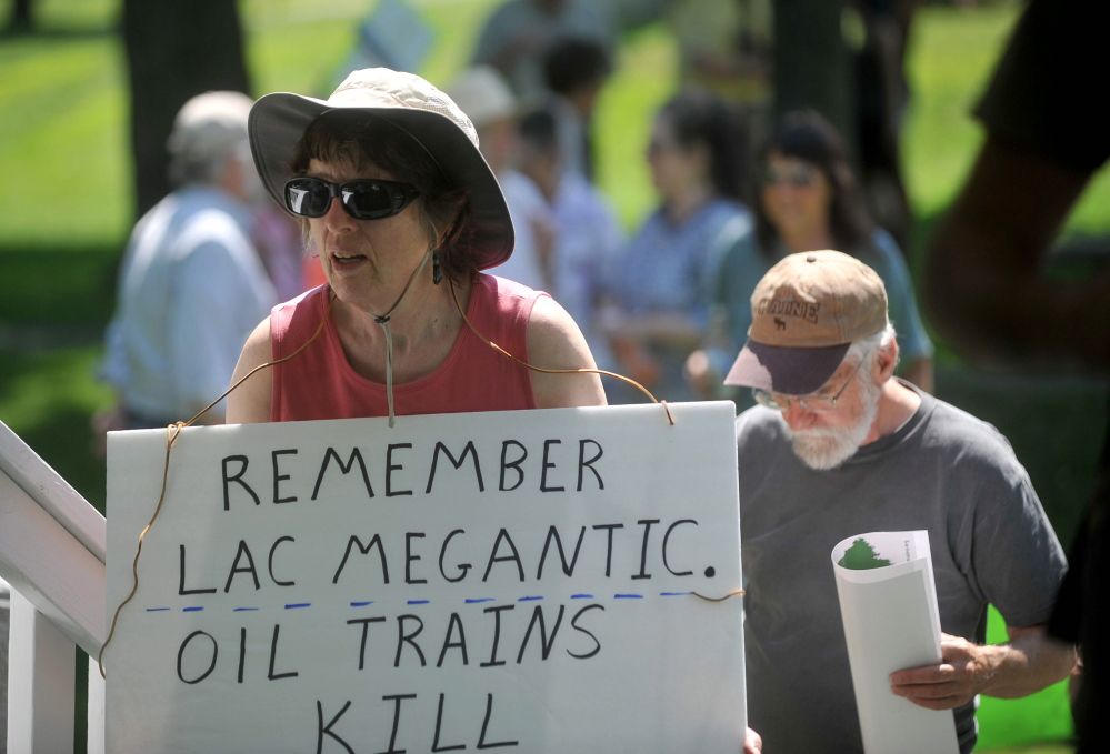 Protesters carrying signs opposing the transport of crude oil by rail gather for a demonstration Saturday in Fairfield.