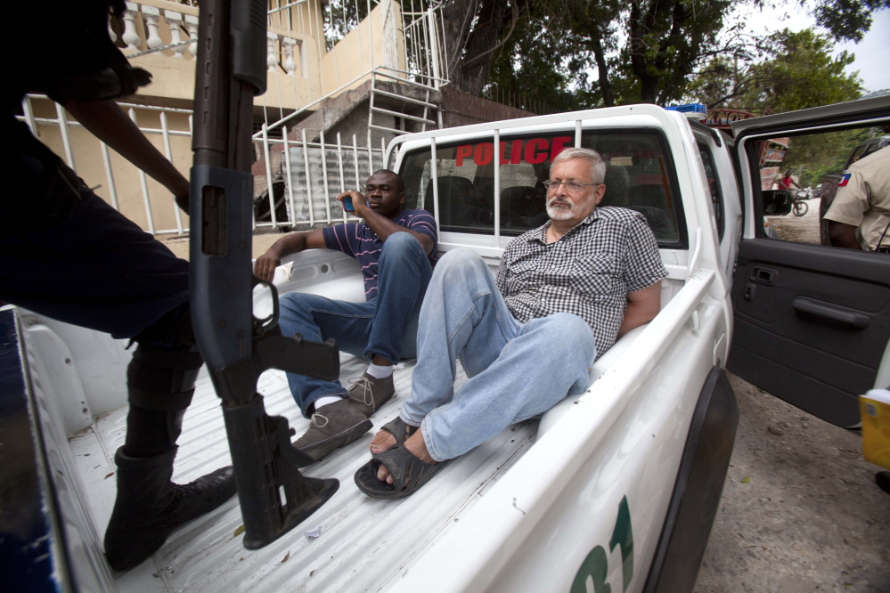 Michael Karl Geilenfeld, right, waits in handcuffs as the manager of his orphanage sits with him in the back of a police truck outside the St. Joseph's Home For Boys in Haiti after his arrest.