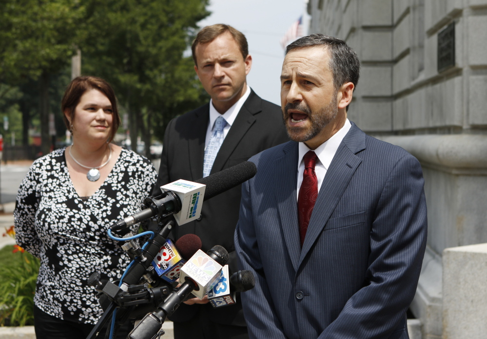 David Webbert, attorney for Maine House Speaker Mark Eves, at rear, speaks to the media outside the federal courthouse in Portland. Webbert said he hopes the court will make Gov. Paul LePage testify under oath in the civil lawsuit filed by Eves. At left is Eves' wife, Laura.