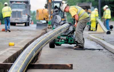 Workers with Bowdoin Excavation lay gas pipes in Augusta in July 2013 for Maine Natural Gas, which is now requesting a rate increase to help cover the cost of expansion into the Augusta area. Andy Molloy/Kennebec Journal