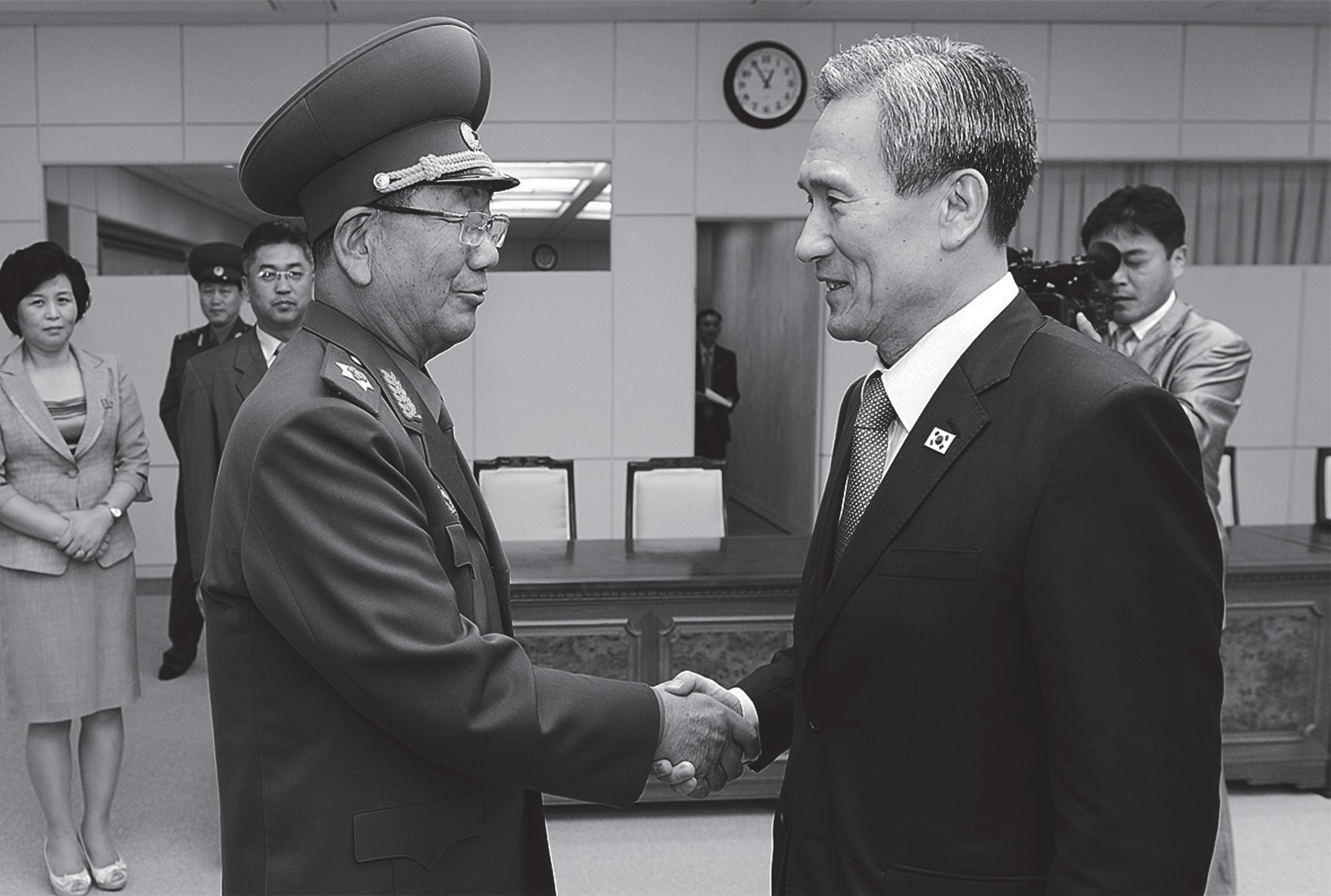 In this photo provided by the South Korean Unification Ministry, South Korean presidential security adviser Kim Kwan-jin, right, shakes hands with Hwang Pyong So, North Korea's top political officer for the Korean People's Army, after their meeting at the border village of Panmunjom in Paju, South Korea on Tuesday.
