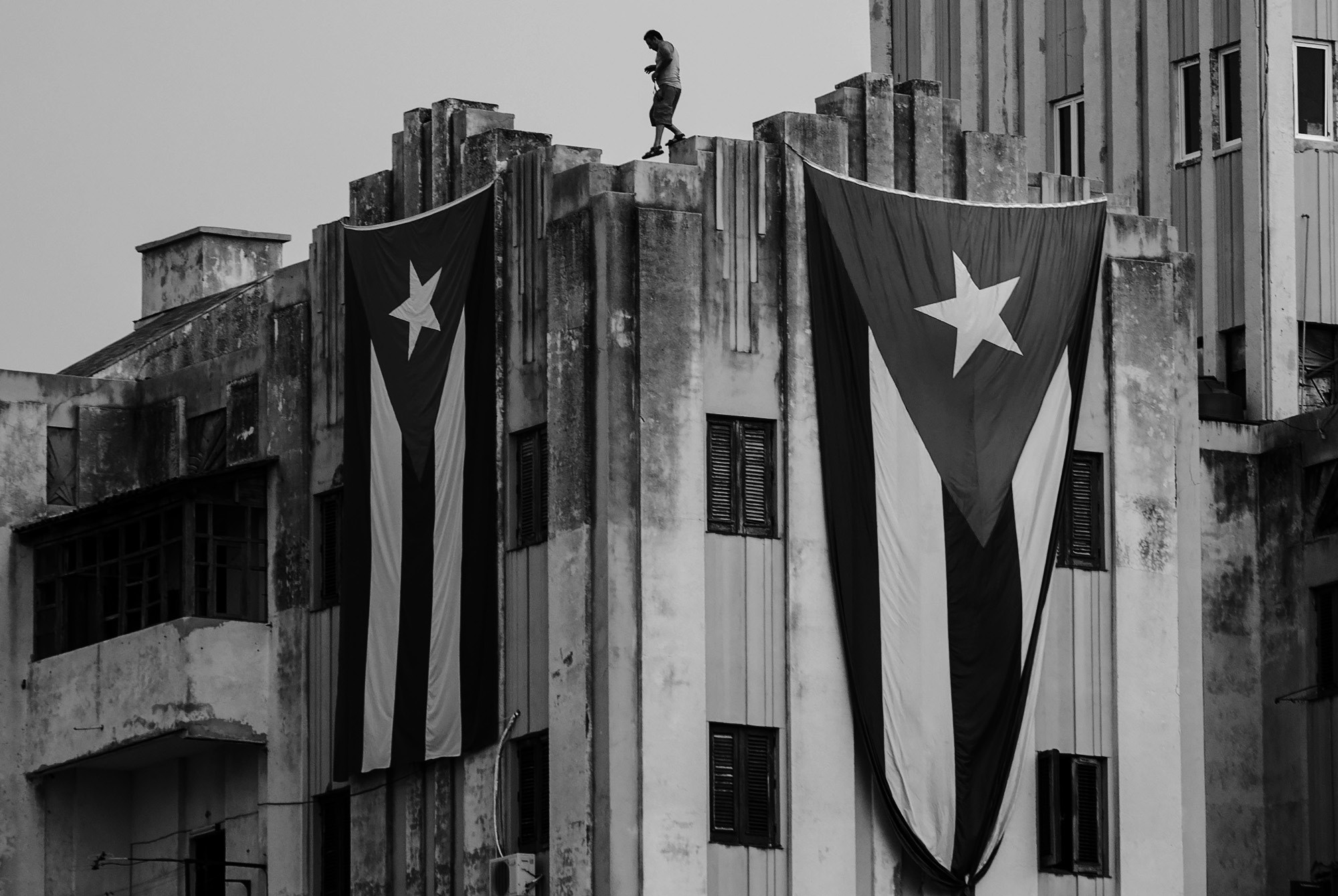 A man walks along the ledge of a building after hanging two giant Cuban flags, next to the U.S. embassy, in Havana, Cuba on Tuesday.