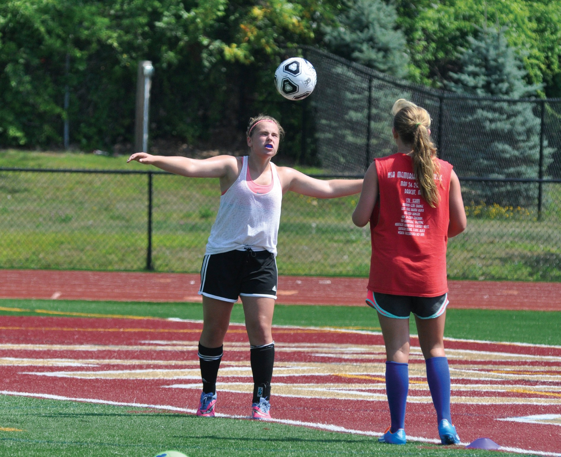 Thornton Academy girls soccer players practice headers during the first day of preseason practices Monday at Hill Stadium in Saco.
