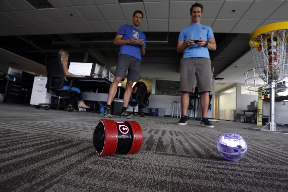 In this July 24, 2015 photo, project managers Bryan Rowe, right, and Bill Cullen, play with Sphero remote controlled toys at Sphero, a fast-growing toy robotics company, in Boulder, Colo.
