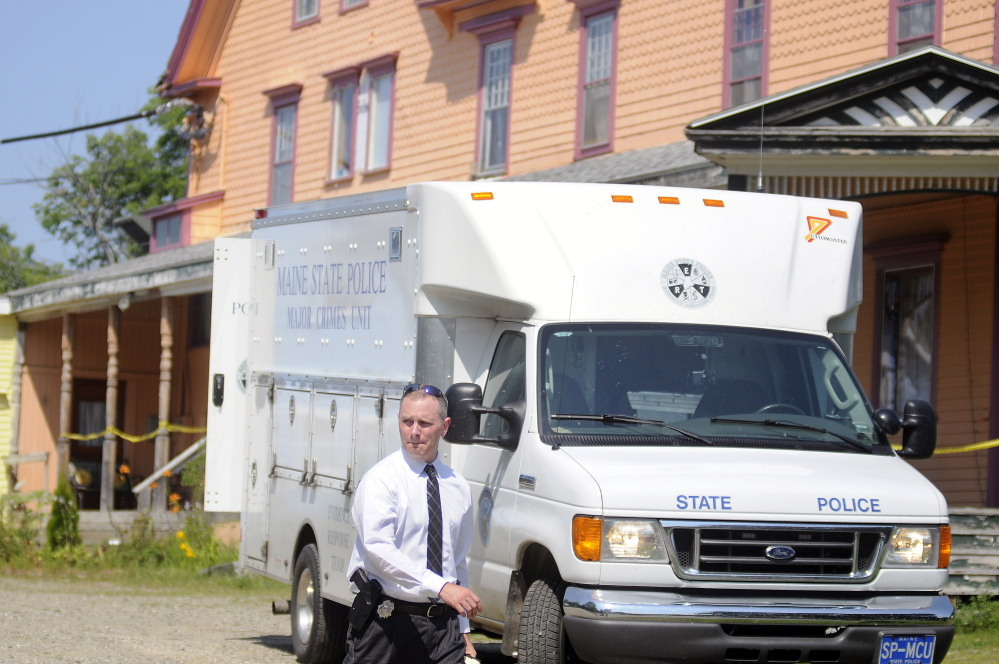 A Maine State Police detective on Sunday walks out of the driveway of an East Pittston boarding house where a fatal stabbing occurred Saturday night.