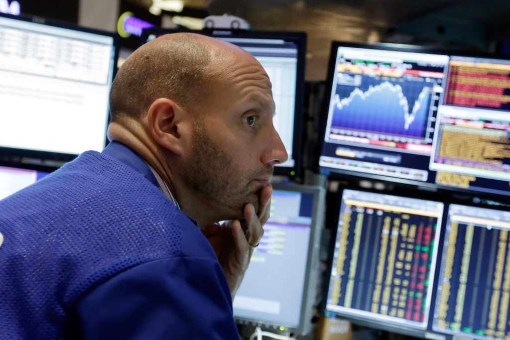Specialist Meric Greenbaum works at his post on the floor of the New York Stock Exchange on Friday, when the markets closed nearly flat after a wild week.