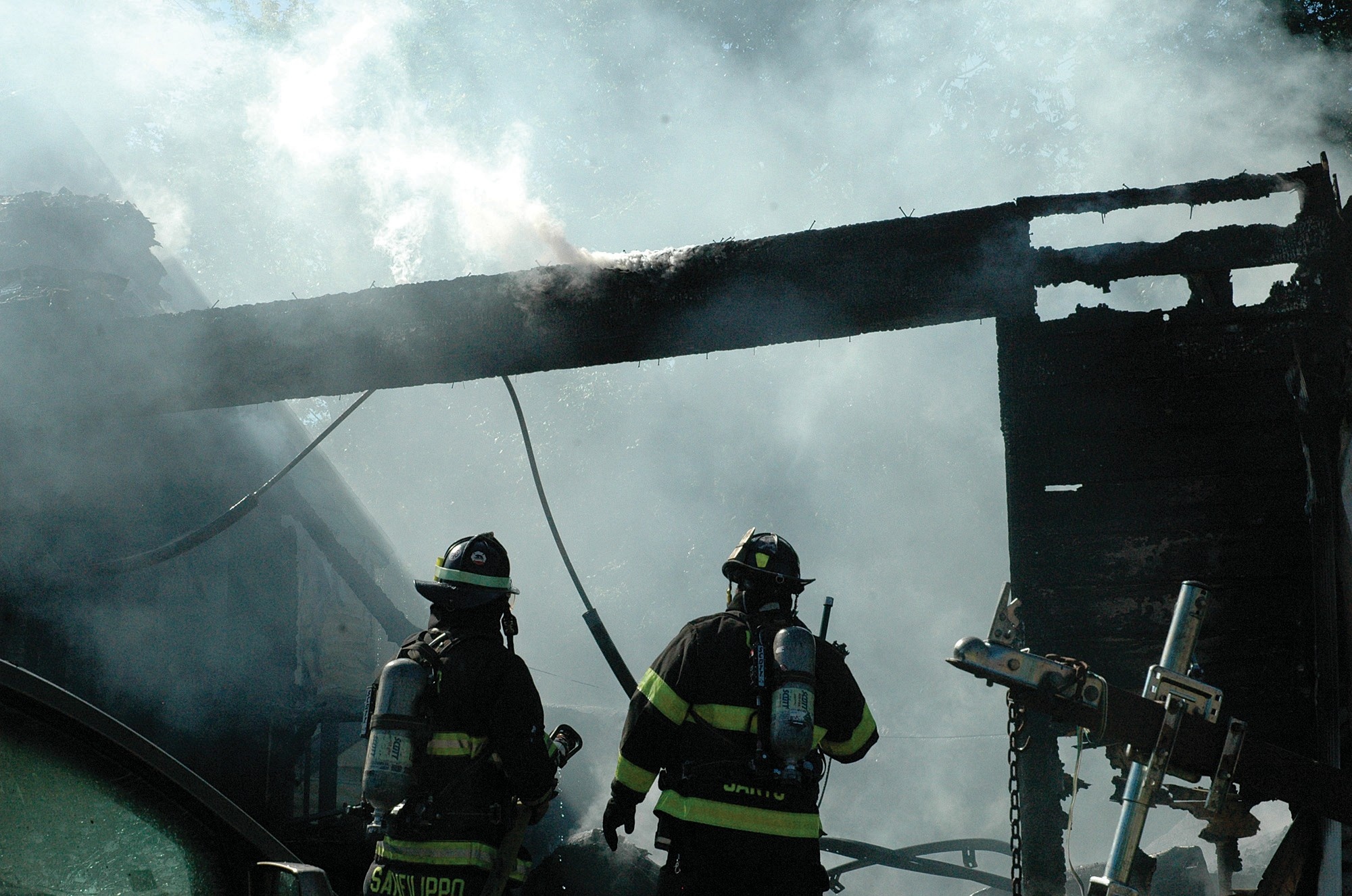 Two firefighters work to extinguish a blaze that destroyed the garage of a home at 387 South St. in Biddeford late Wednesday morning.
