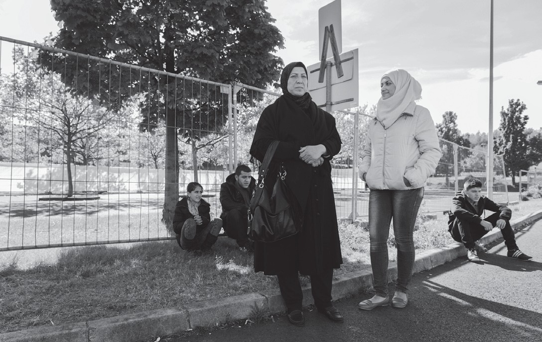 In this Sept. 22 photo, from left, Raghad, Mohammed, mother Khawla Kareem, Reem and Yaman, a refugee family from Syria, wait outside an asylum seekers shelter in Heidenau, near Dresden in eastern Germany.