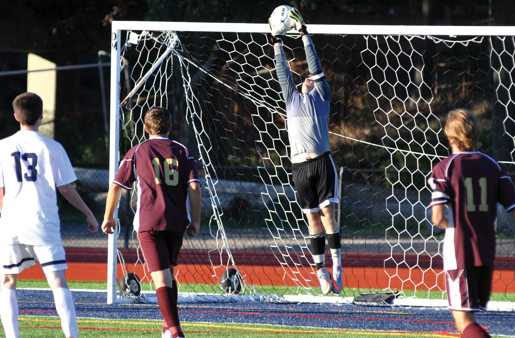 Thornton Academy goalie Andrew Coleman makes a leaping save during the first half of the Trojans' 0-0 draw with Portland at Fitzpatrick Stadium Tuesday.