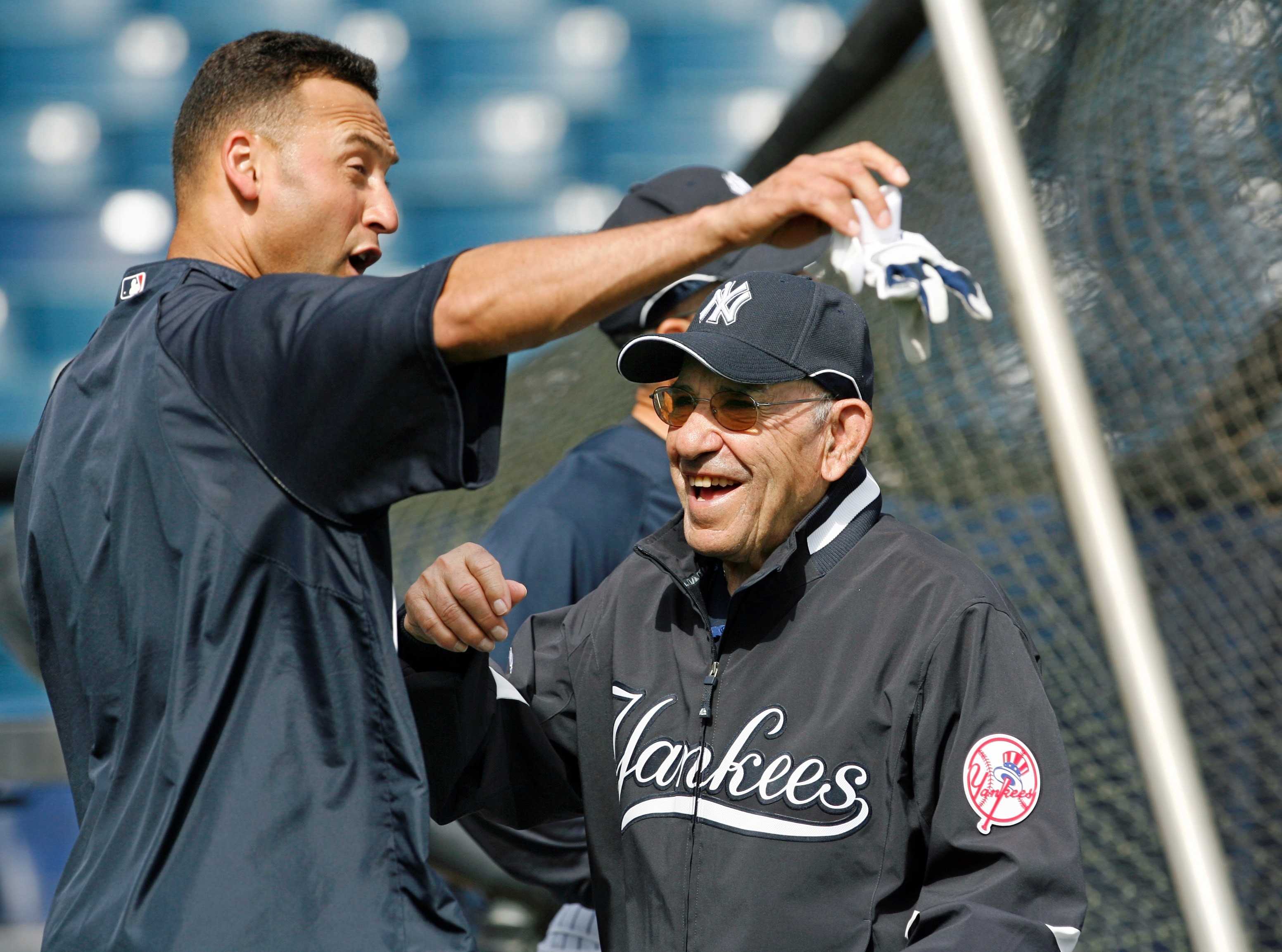 This March 7, 2008, file photo shows New York Yankees shortstop Derek Jeter, left, and Yogi Berra clowning around by the batting cage before the Yankees spring training baseball game against the Houston Astros at Legends Field in Tampa.