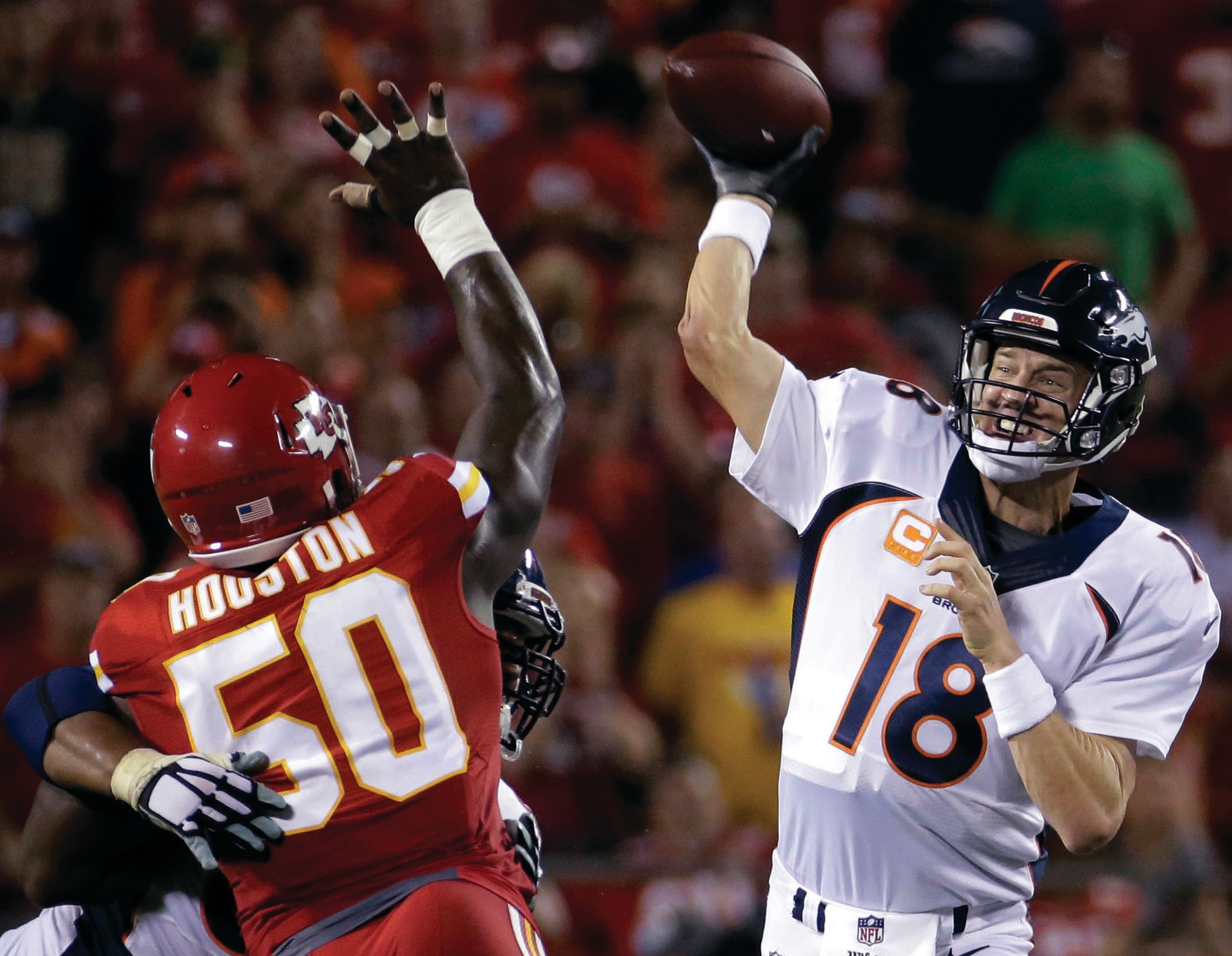 Denver Broncos quarterback Peyton Manning (18) throws under pressure from Kansas City Chiefs linebacker Justin Houston (50) during the second half of an NFL football game in Kansas City, Mo. Thursday.