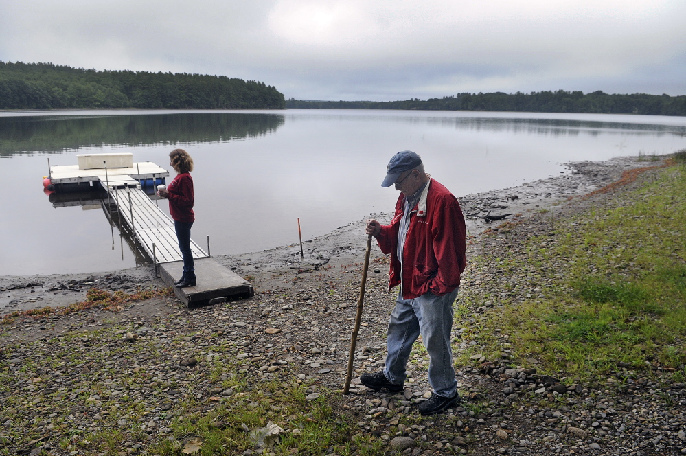 Stan Whittier walks on the shore of Clary Lake in Jefferson while his daughter, Jane Roy, stands on the family's dock. It's been nearly three years since property owners around Clary Lake in Jefferson and Whitefield appealed to the state to intervene over a low water level, and residents say the situation still hasn't improved.