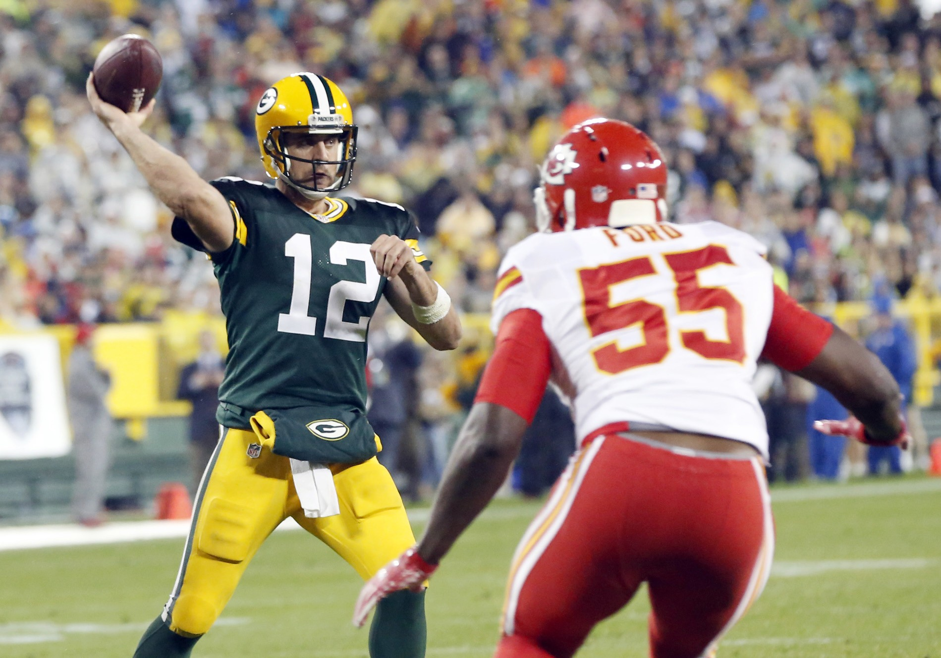 Green Bay Packers' Aaron Rodgers throws with Kansas City Chiefs' Dee Ford (55) rushing during the second half of an NFL football game Monday in Green Bay, Wis.