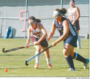 FREEPORT HIGH SCHOOL'S Maya Bradbury (7) and Poland's Morgan Brousseau (30) both reach for the ball in a Western Maine Conference field hockey matchup on Thursday. The Knights downed the Falcons, 1-0, in overtime.