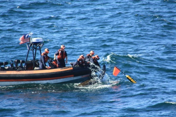 Crew members in a small boat deployed from the U.S. Coast Guard cutter Campbell untangle a 6-foot-long leatherback turtle from fishing line 15 miles off Cape Elizabeth on Sunday. After cutting the line, the crew watched as the turtle swam away to the open sea.