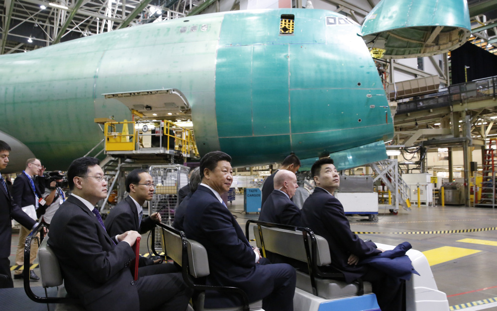 Chinese President Xi Jinping, center, tours the Boeing assembly line Wednesday in Everett, Wash. Boeing said that Chinese companies have agreed to buy 300 jets and build an aircraft assembly plant in China.