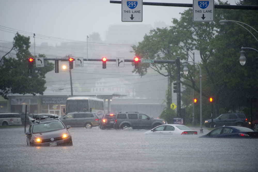 Disabled cars sit in water at the corner of Franklin and Somerset streets in Portland during Wednesday's deluge. Flooding has been a problem in the area for decades, but the city has yet to take aggressive steps to address it. Gabe Souza/Staff Photographer
