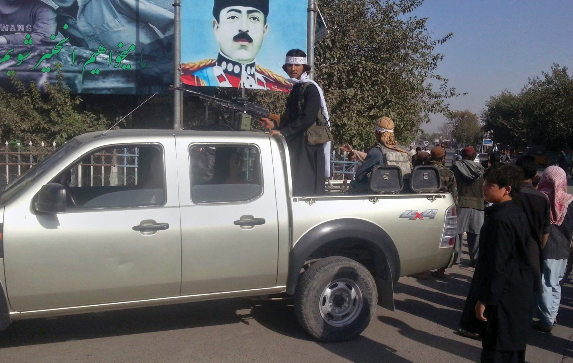 In this Sept. 29 photo, a Taliban fighter stands guard on a vehicle in Kunduz, north of Kabul, Afghanistan.