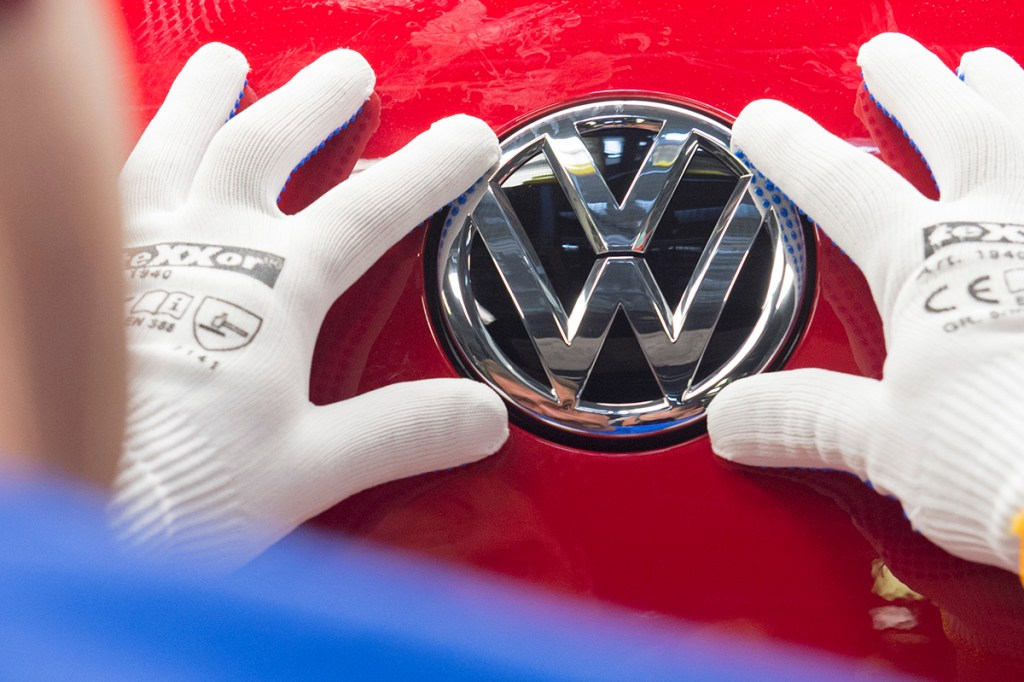 """A worker checks the Volkswagen badge on a Golf car in this In this Sept. 6, 2015, photo. . Above and beyond legal problems, the  company's growing emissions scandal is a huge problem for a brand long identified with trustworthiness and reliability. And there are concerns that could spill over into a wider image problem for goods """"made in Germany."""" The Associated Press"""