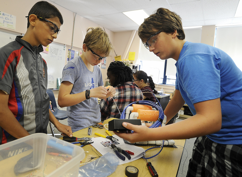 King Middle School students Ameer Alasadi, 12, Evan Haapala, 12, and Josh Willey, 13, at work building submersible devices for scientific research.