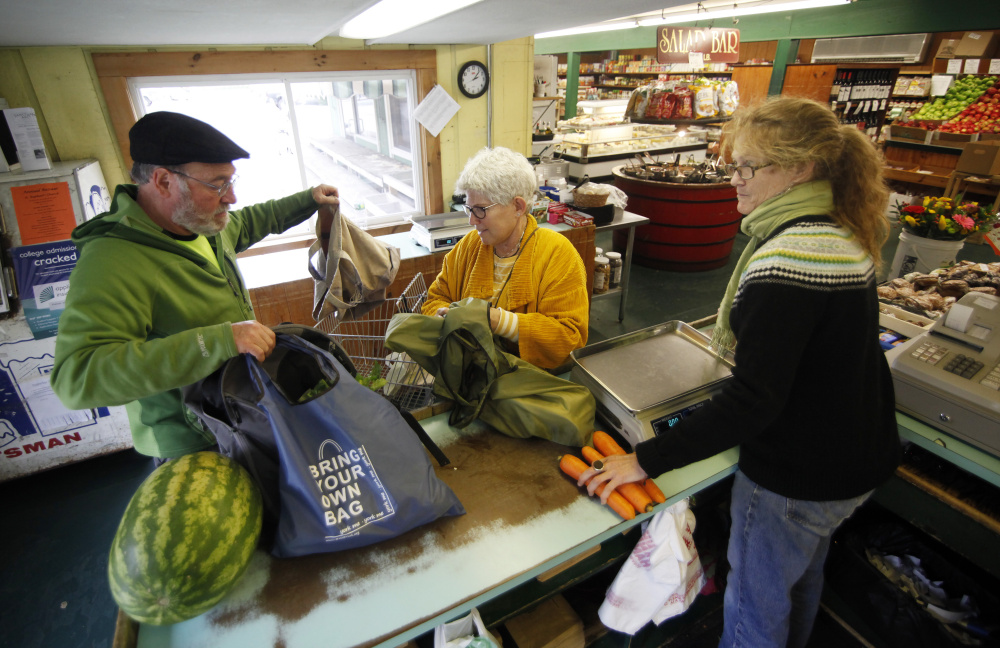 Victoria Simon, center, and her husband, Michael Modern, they check out at the Golden Harvest in Kittery, assisted by cashier Ashley Kehrig.