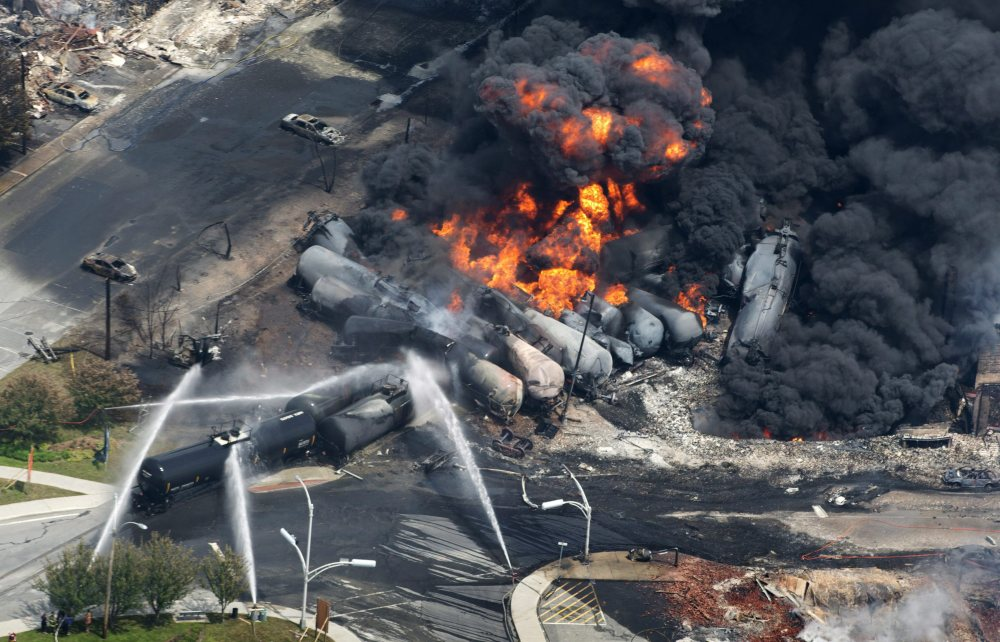 Smoke rises from railway cars carrying crude oil after the deadly derailment in Lac-Megantic, Quebec, on July 6, 2013.